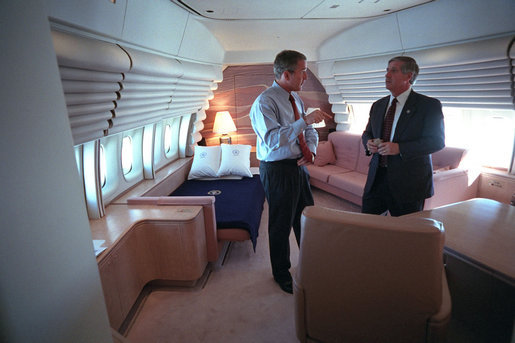 President George W. Bush confers with White House Chief of Staff Andrew Card aboard Air Force One