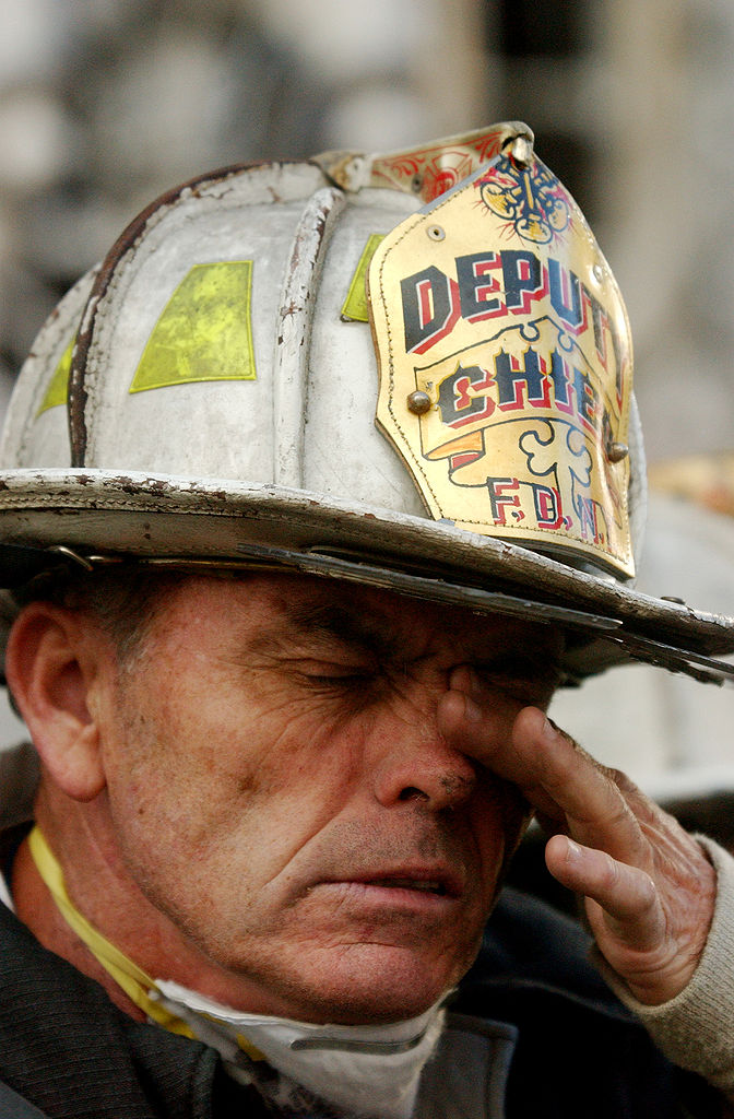 A firefighter tries to clear his eyes of soot during rescue effort at the WTC, 14 Sept 2001