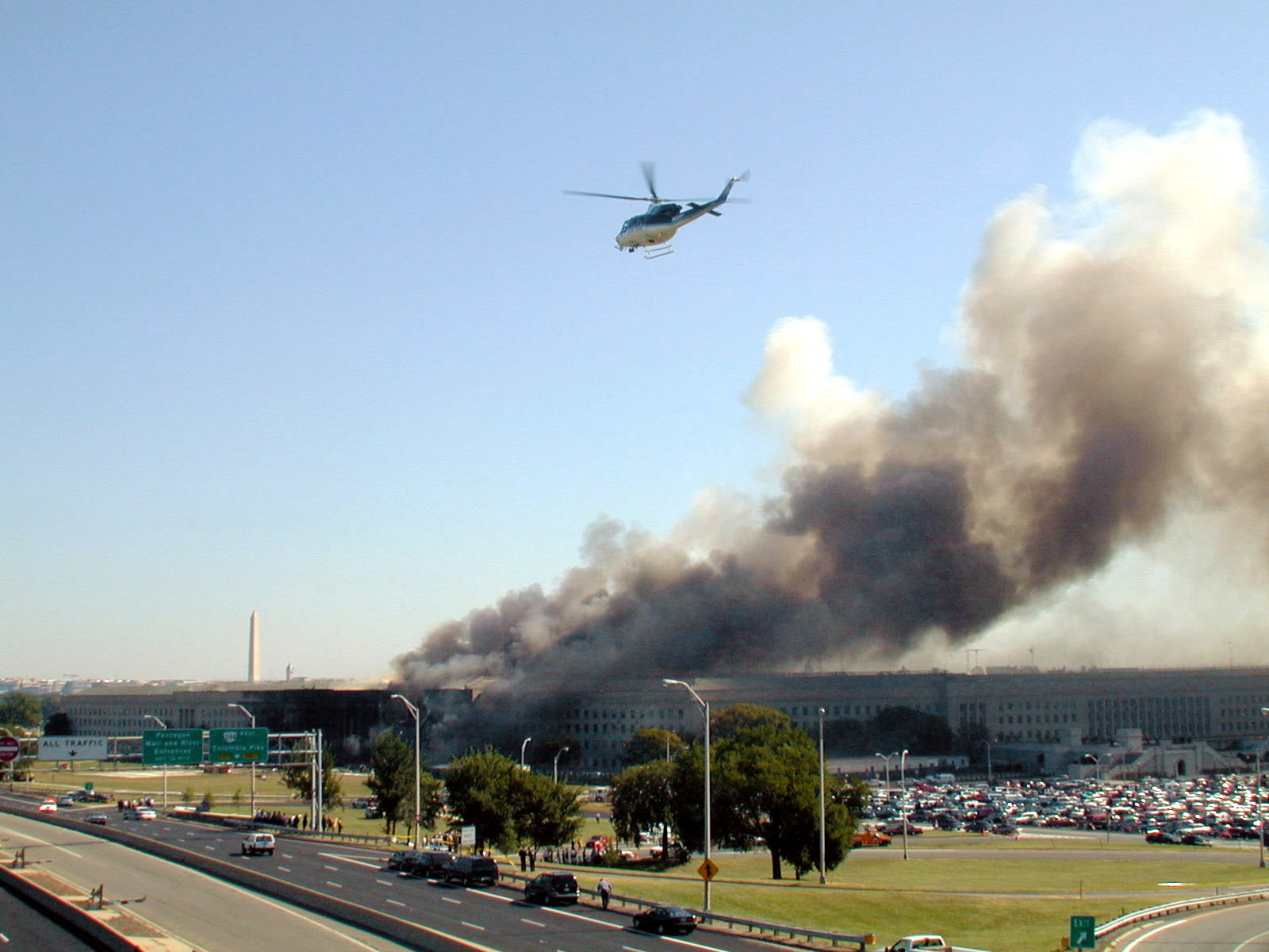 A helicopter flies over the area as smoke pours from the southwest corner of the Pentagon Building
