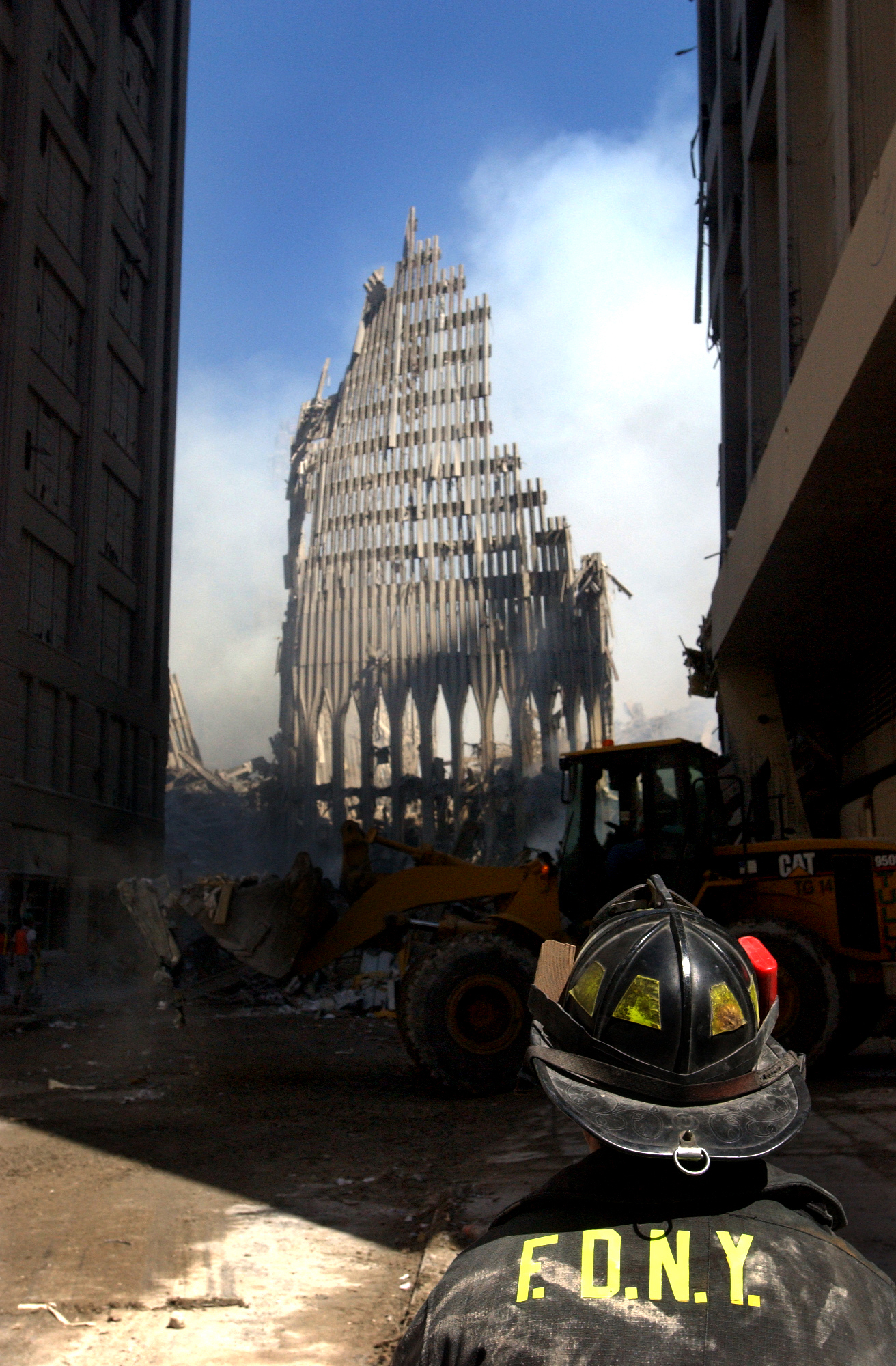 A firefighter looks at the World Trade Center in ruins, 13 September 2001