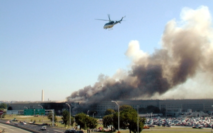 A helicopter flies over the area after Flight 77 crashes into the Pentagon time